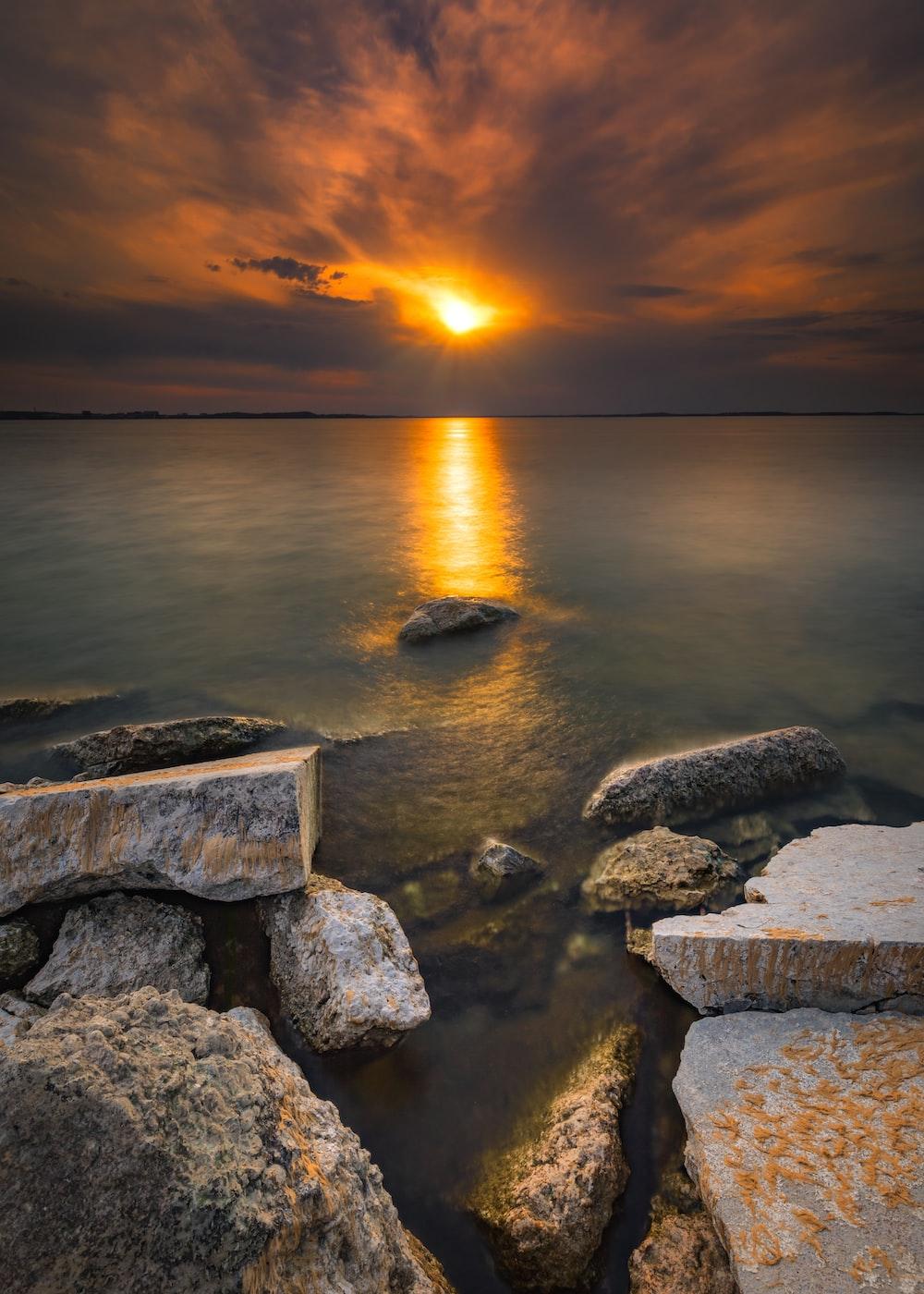 gray rocks on sea during sunset