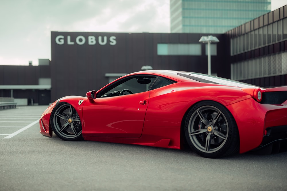 red ferrari 458 italia parked on gray pavement