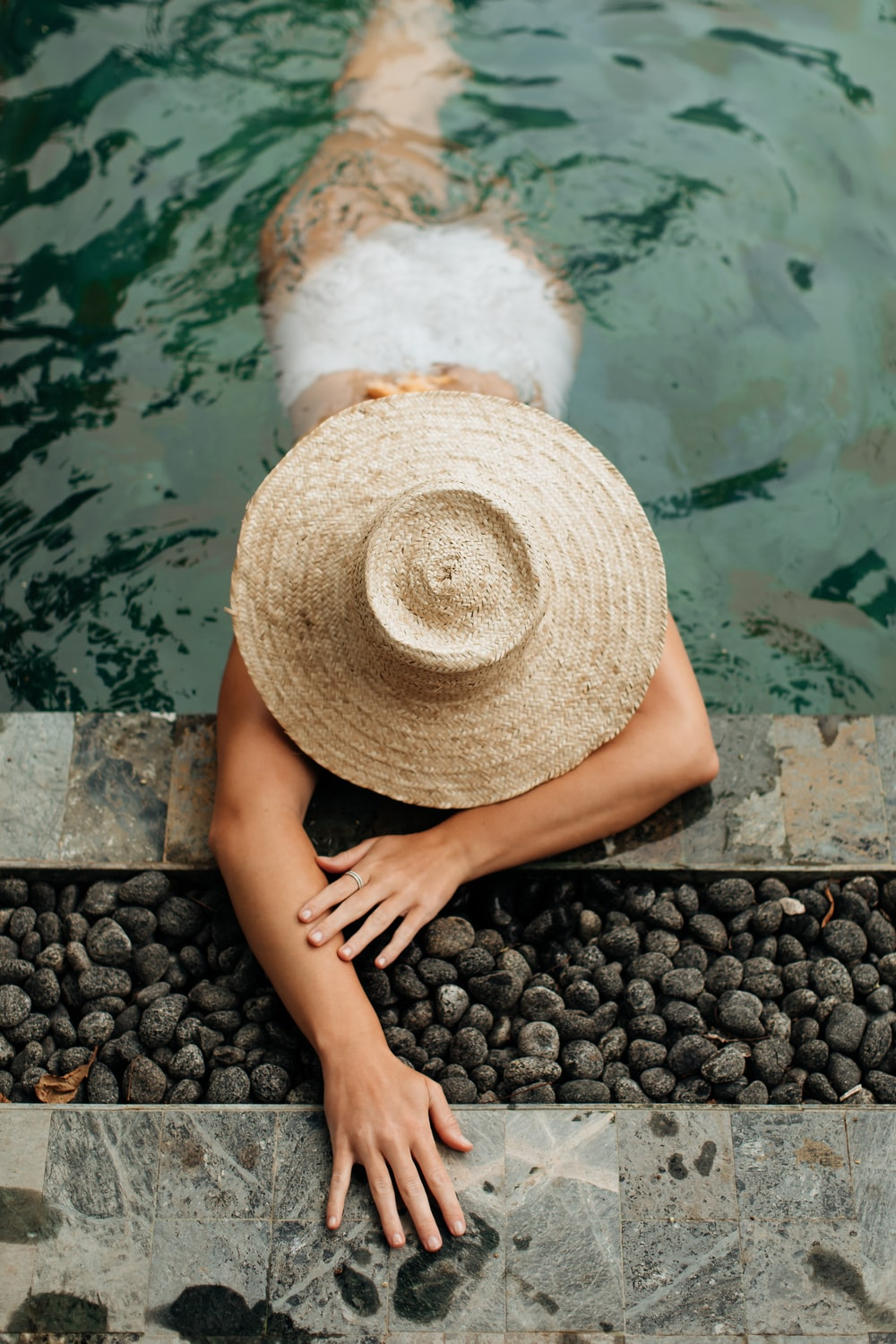 person wearing brown straw hat sitting on black stones near body of water during daytime