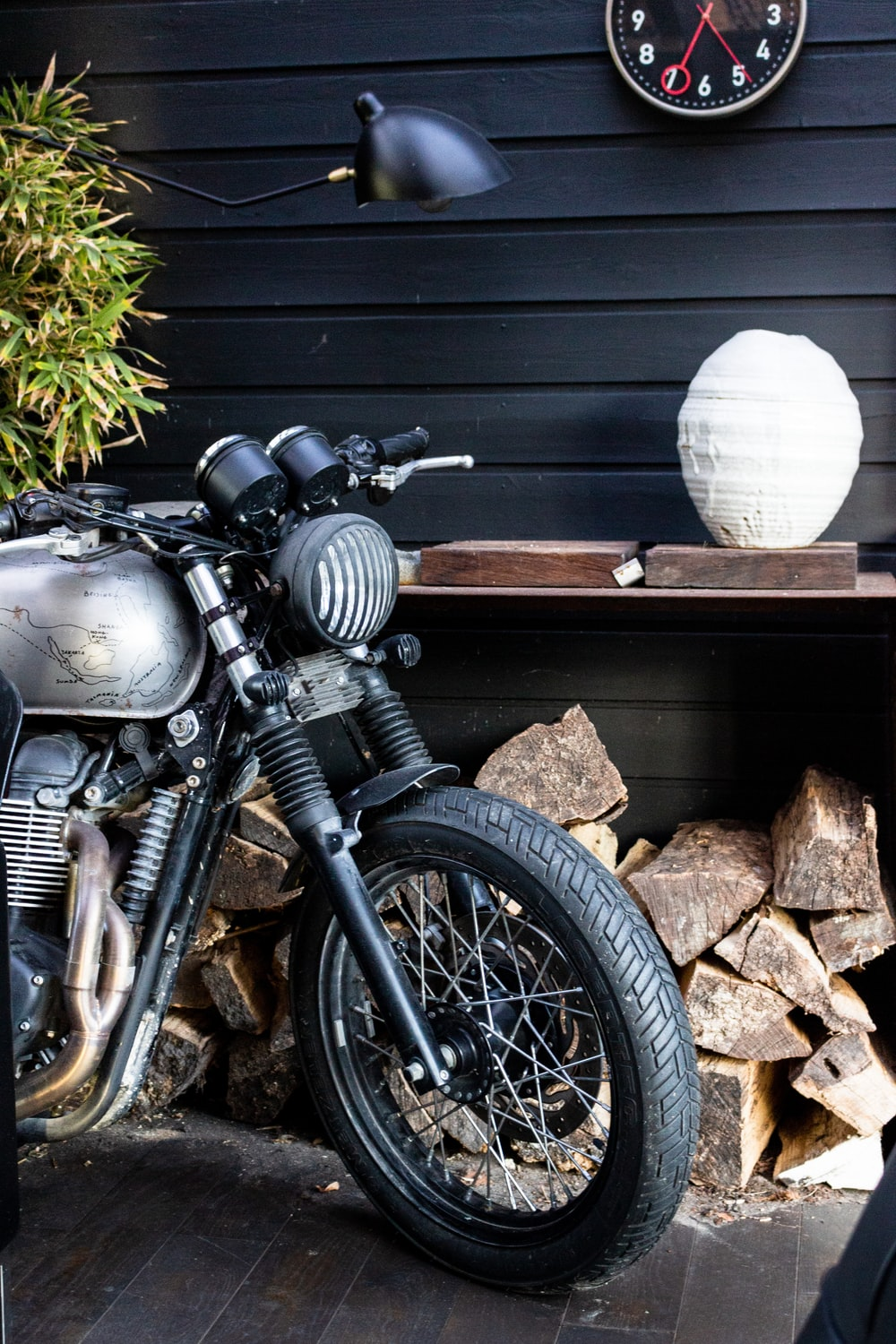 black motorcycle parked beside gray wooden wall