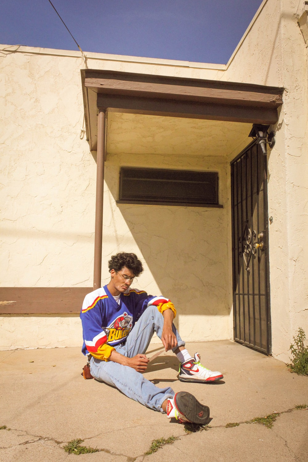 man in blue and white long sleeve shirt sitting on brown concrete stairs during daytime