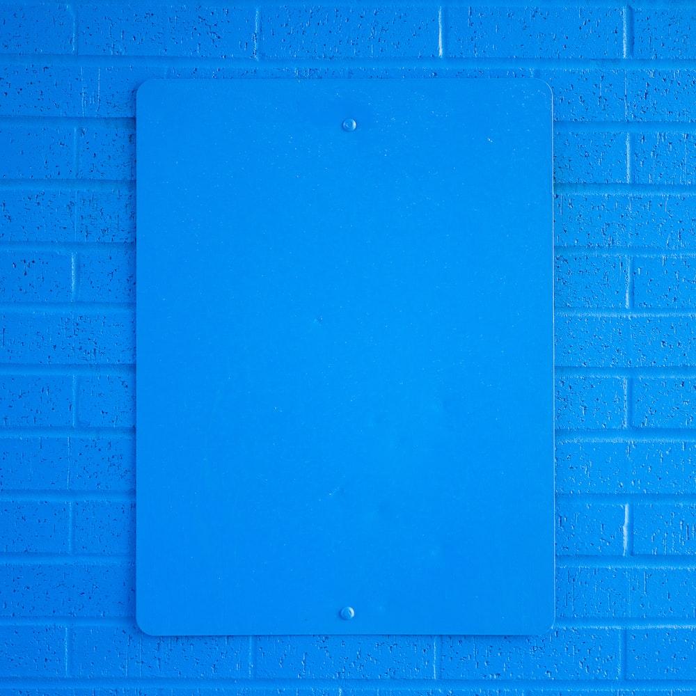 blue ipad on purple brick wall