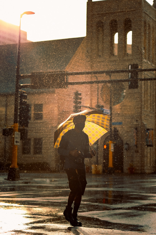 person in black jacket holding umbrella walking on street during rain