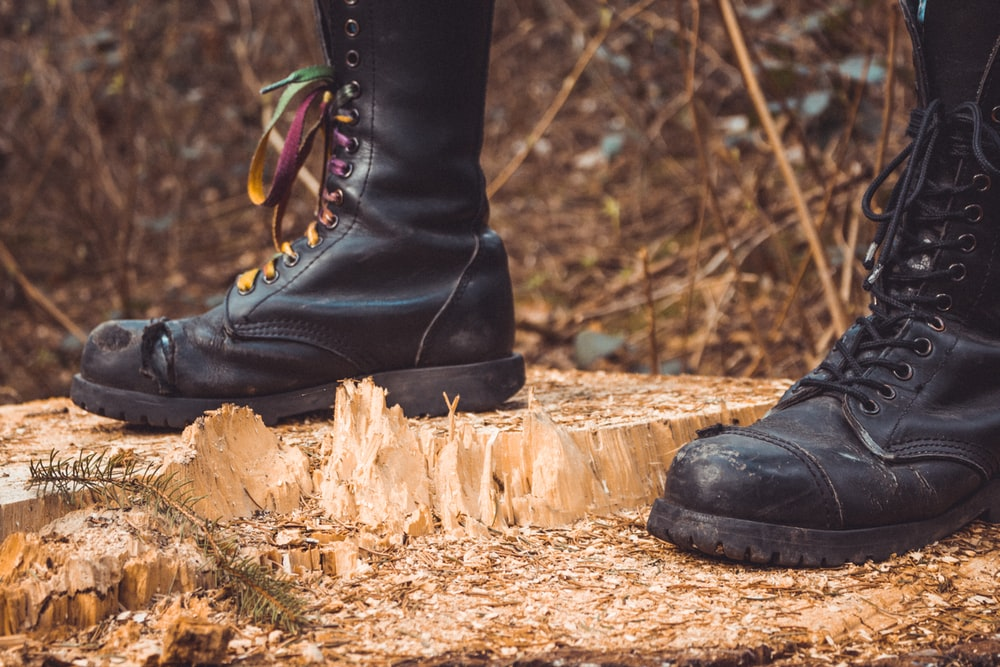 person wearing black leather boots standing on brown wood log