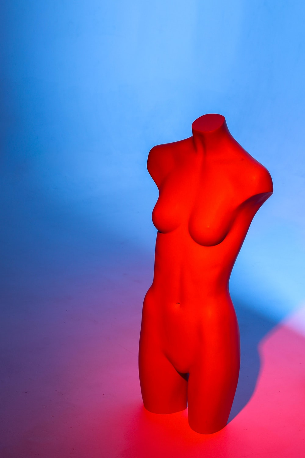red human body figurine on white surface