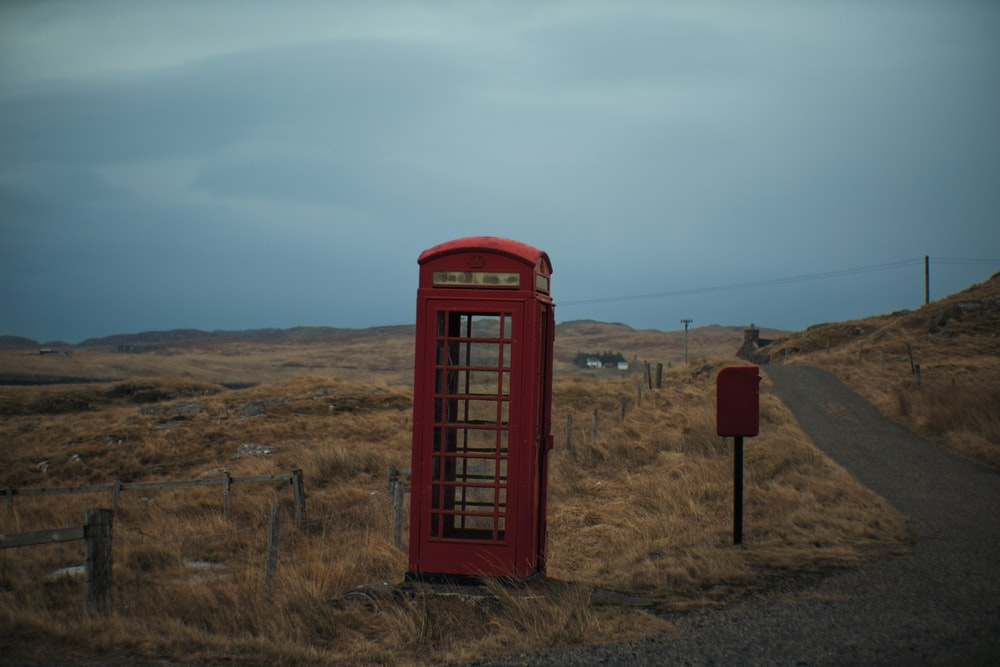 red telephone booth on brown grass field under blue sky during daytime