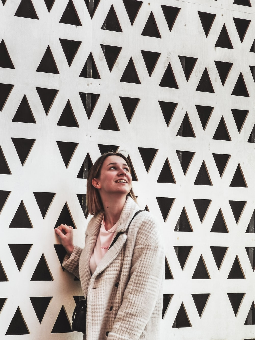 woman in white knit sweater standing beside white wall