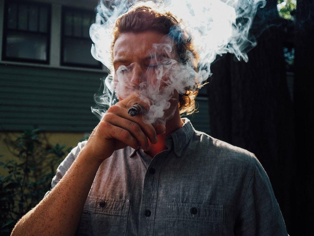 man in gray button up shirt smoking
