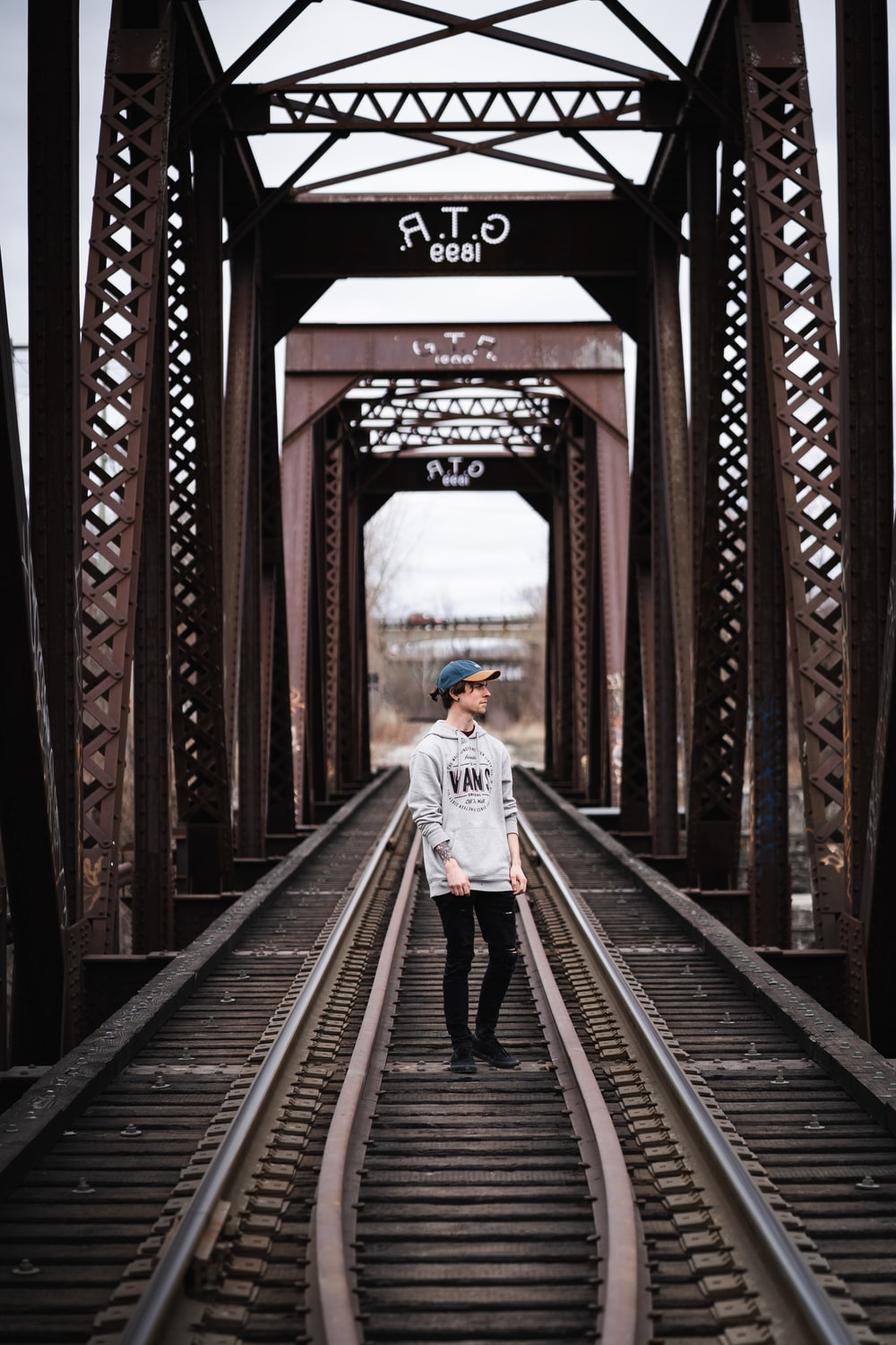 woman in white jacket walking on train rail