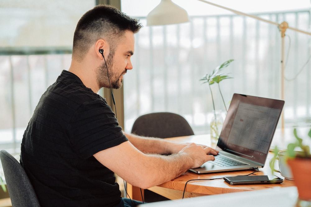 man in black t-shirt using laptop computer