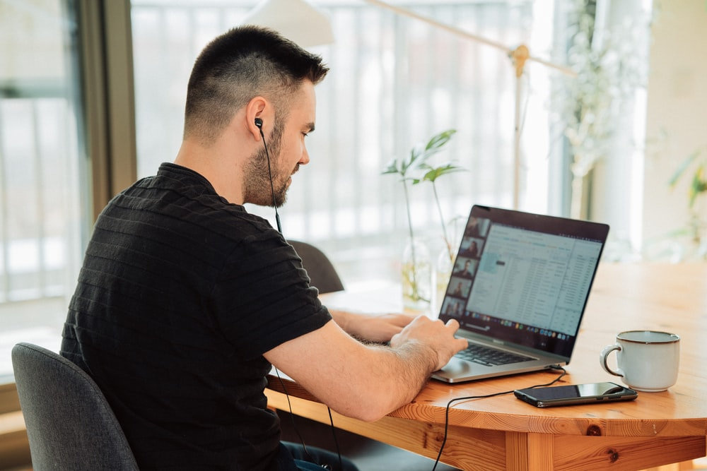 man in black t-shirt using macbook pro