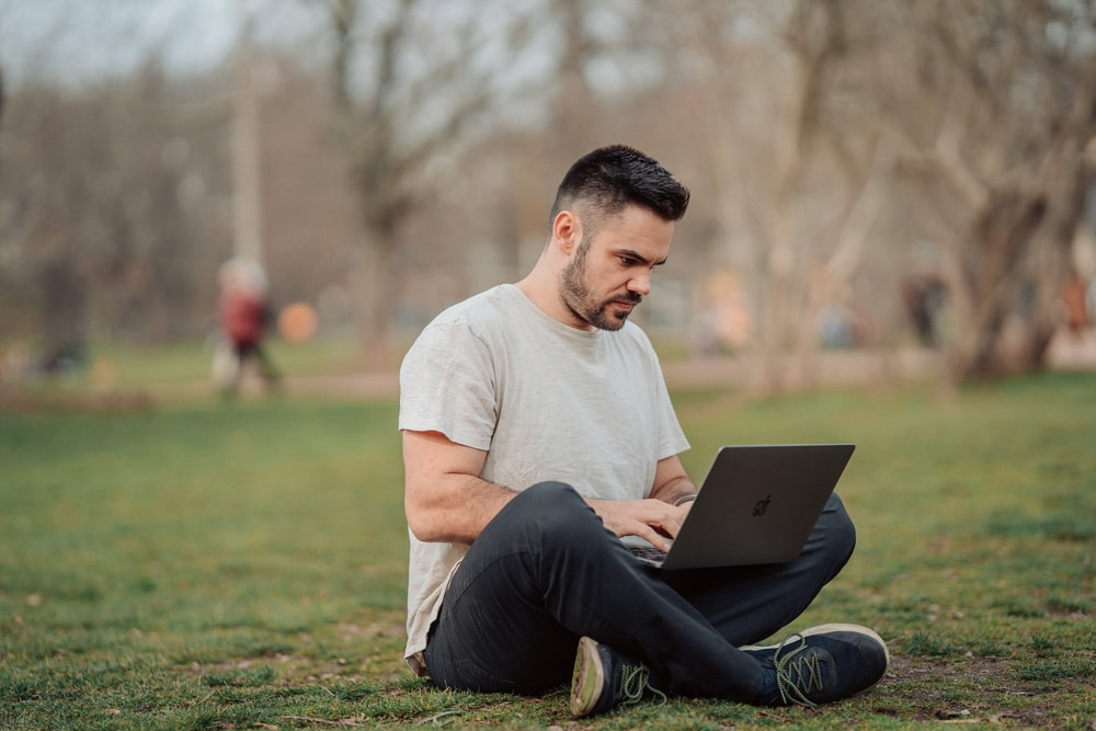 man in white crew neck t-shirt and black pants sitting on green grass field using