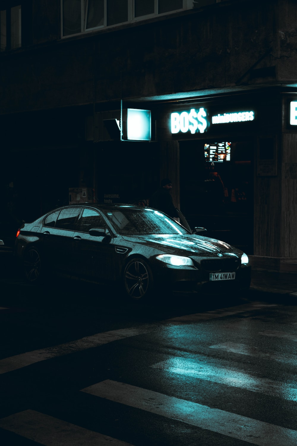 black mercedes benz coupe parked beside the building during night time