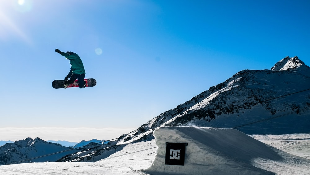 person in green jacket and black pants riding black snowboard on snow covered mountain during daytime