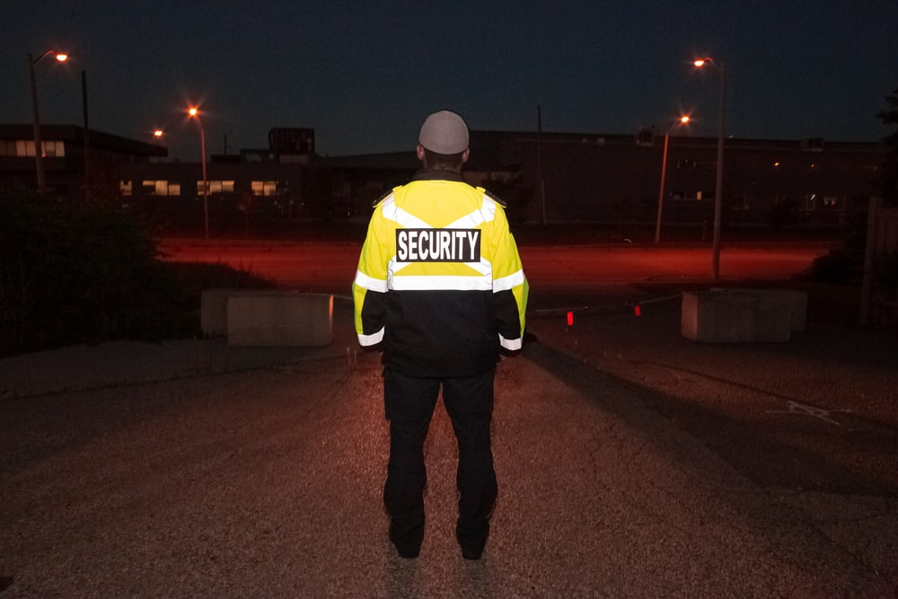 man in yellow and black jacket standing on sidewalk during night time