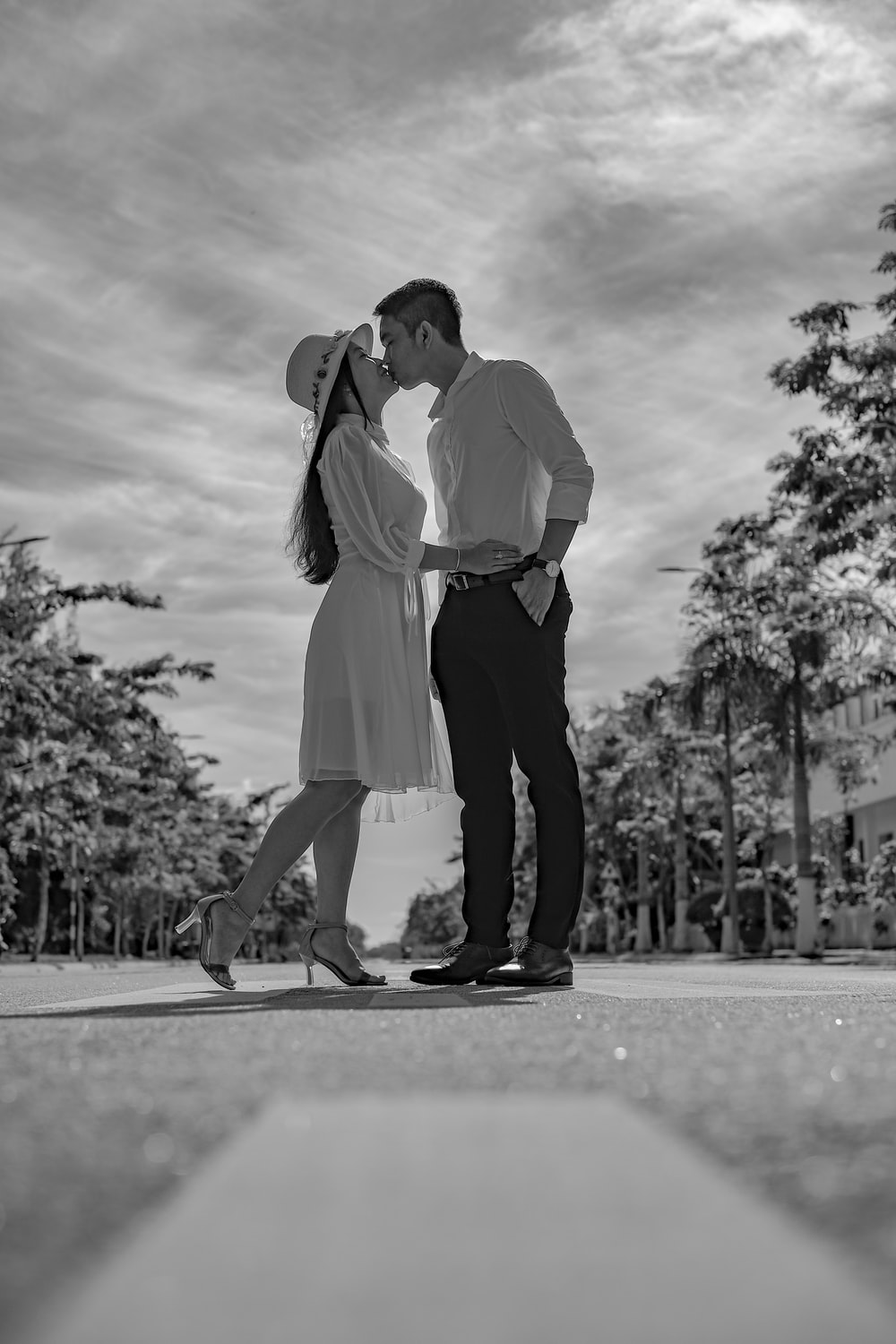 man and woman kissing on the road in grayscale photography