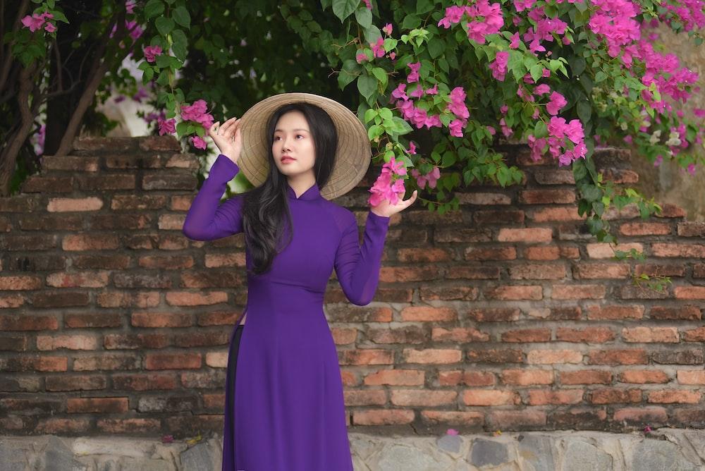 woman in purple long sleeve dress standing beside purple flowers