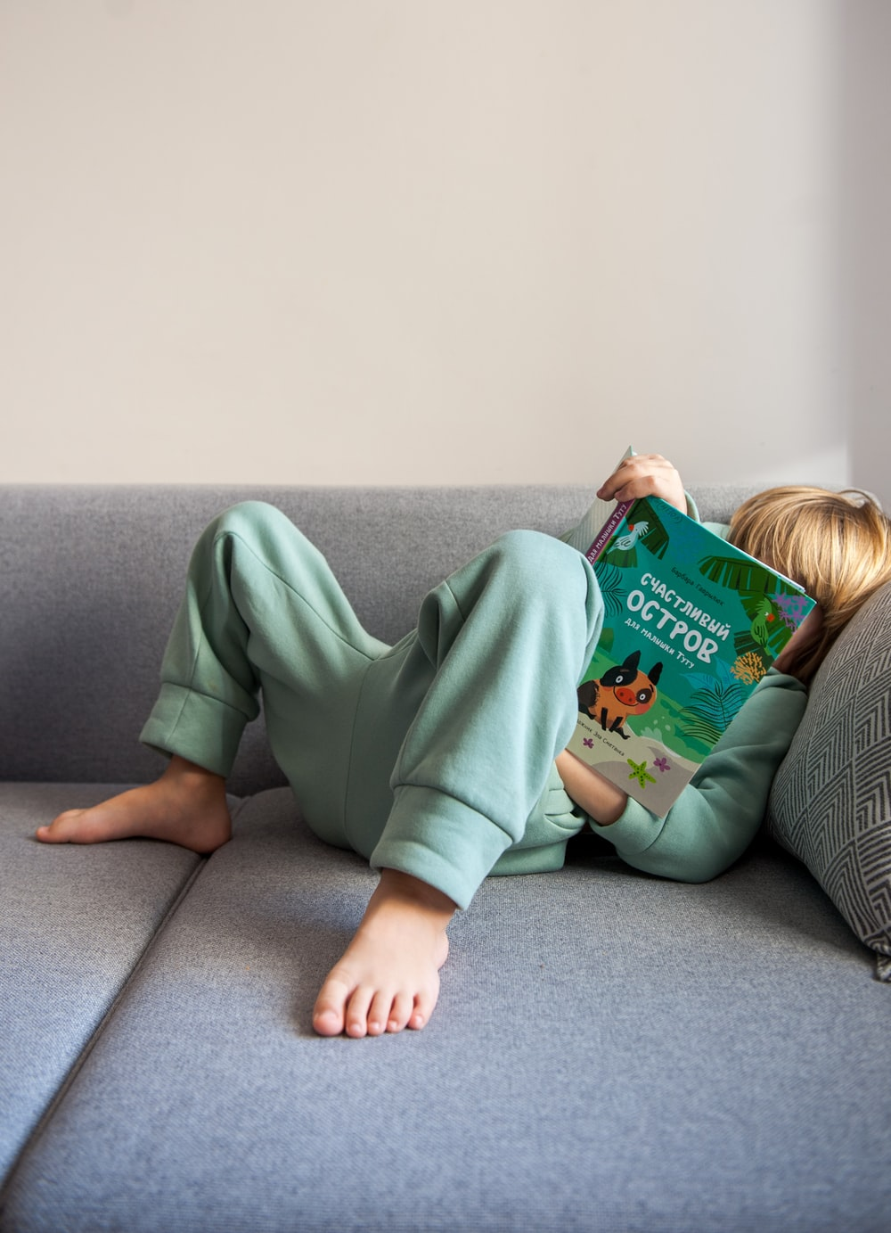 girl in green long sleeve shirt lying on gray couch