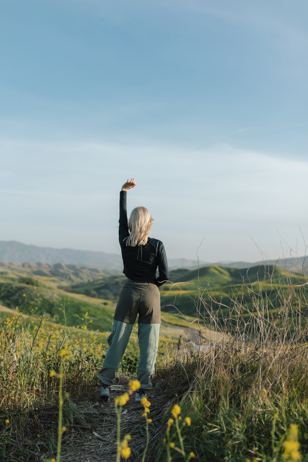woman in black long sleeve shirt and blue denim jeans standing on green grass field during