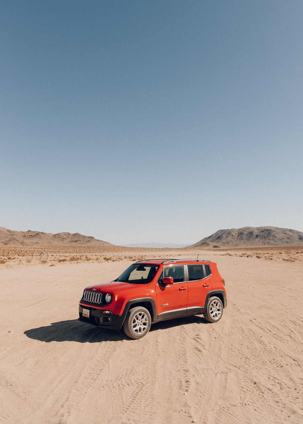 Red Suv On Brown Sand Under Blue Sky During Daytime Photo Free Giant Rock Image On Unsplash