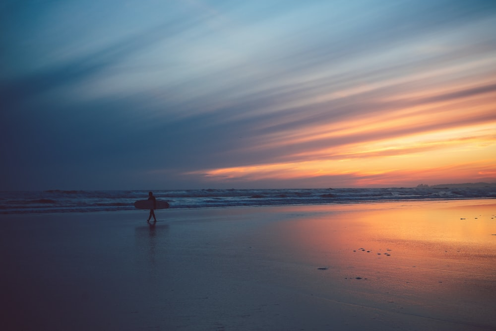 person in body of water during sunset
