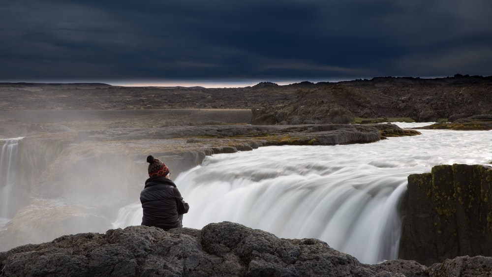 man in red jacket sitting on rock near waterfalls during daytime