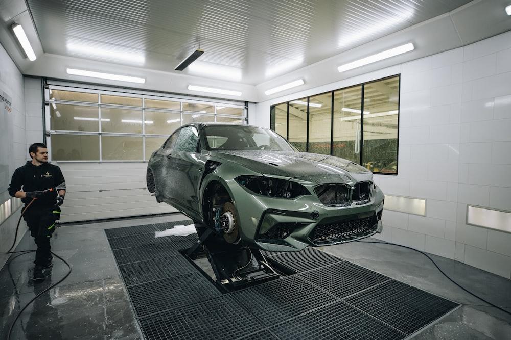green sports car parked in garage