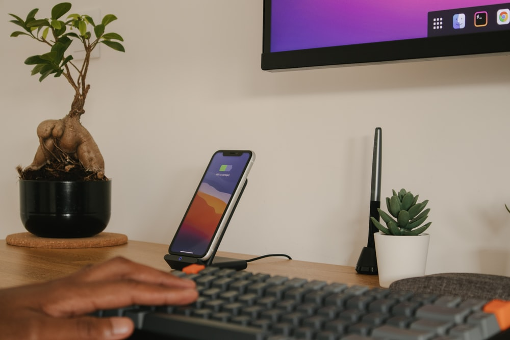 person holding iphone 6 near black computer keyboard
