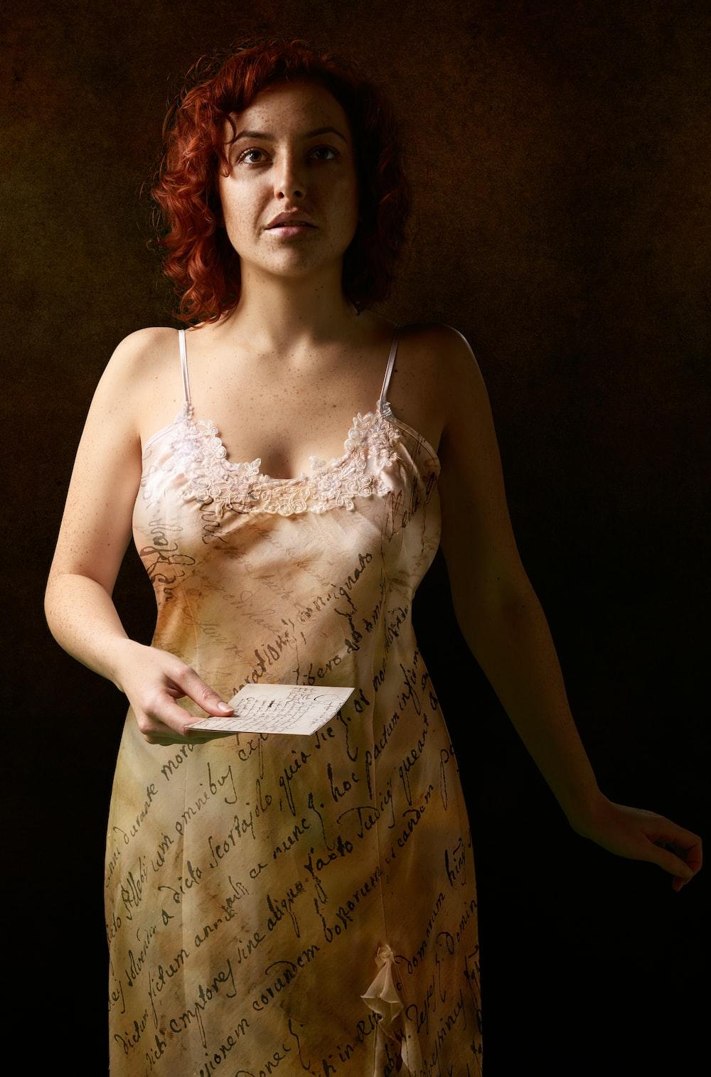 woman in white spaghetti strap dress holding white paper