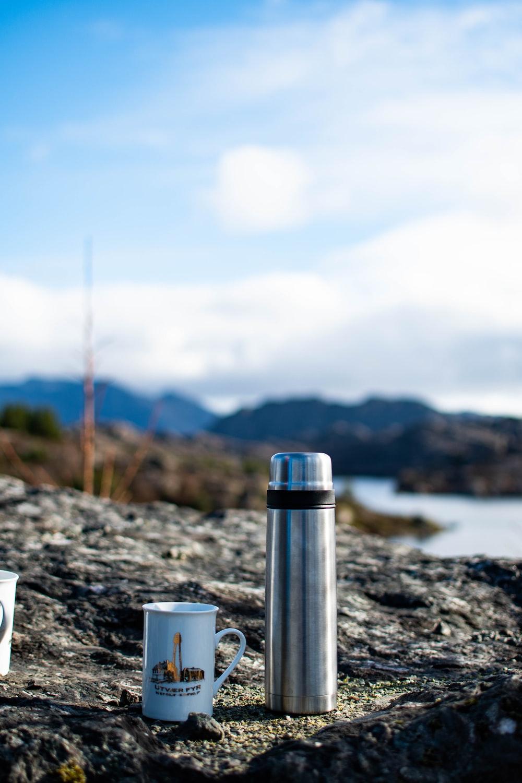 white ceramic mug on gray rock near body of water during daytime
