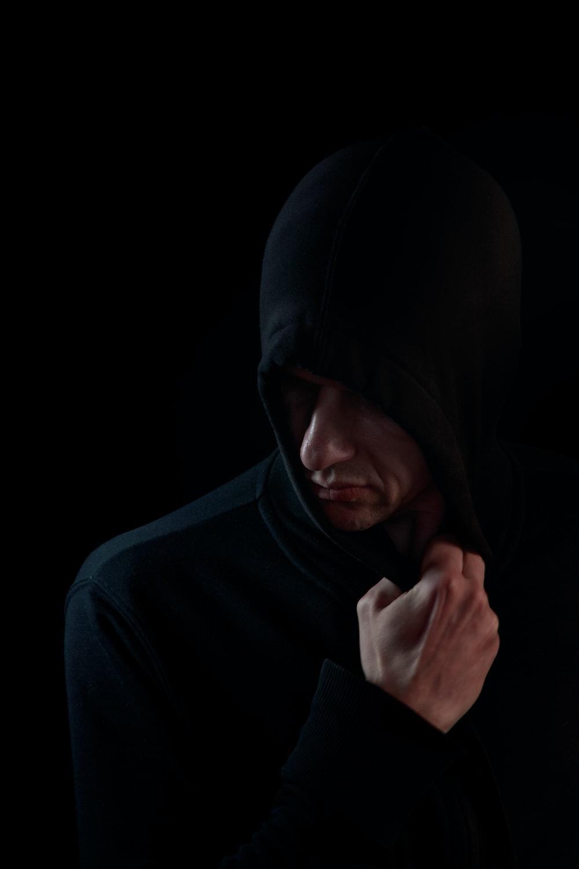 man in black hoodie covering his face