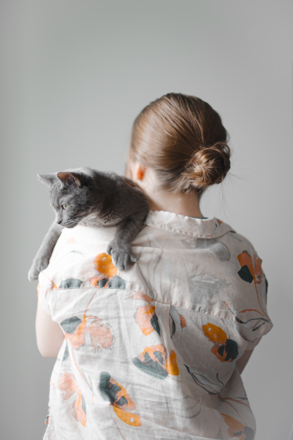 girl in white and orange floral dress hugging gray cat