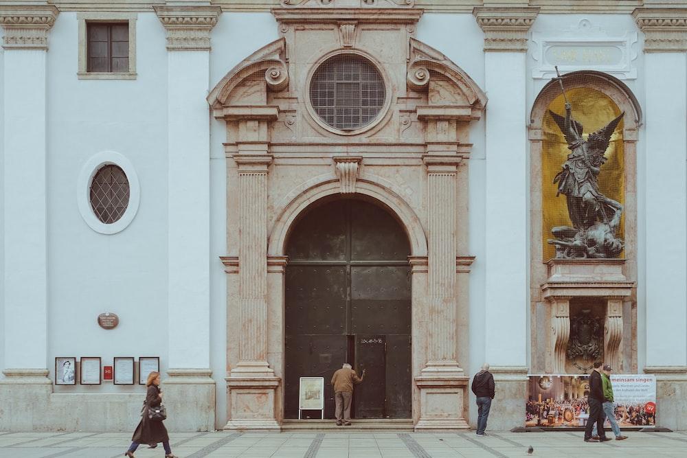 man in black jacket walking near brown wooden door during daytime