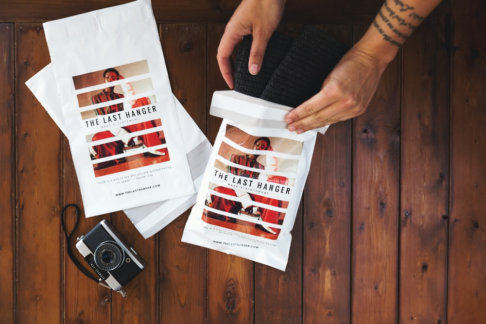 person holding white and red paper
