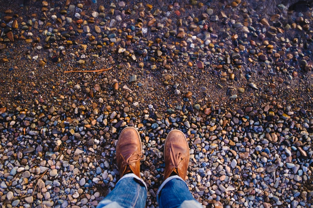 person in blue denim jeans and brown leather shoes standing on rocky ground