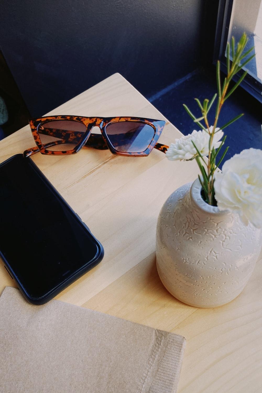 black android smartphone beside white ceramic vase with white flower