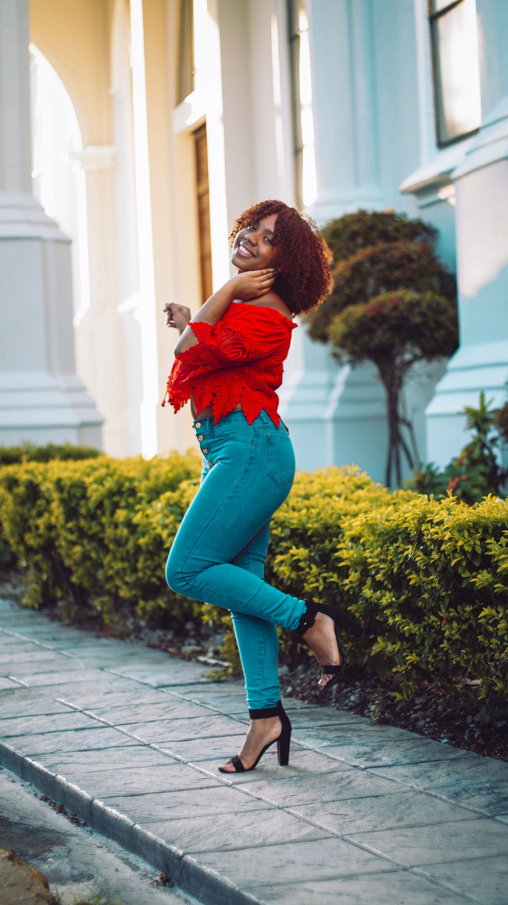 woman in red shirt and blue denim jeans standing on pathway