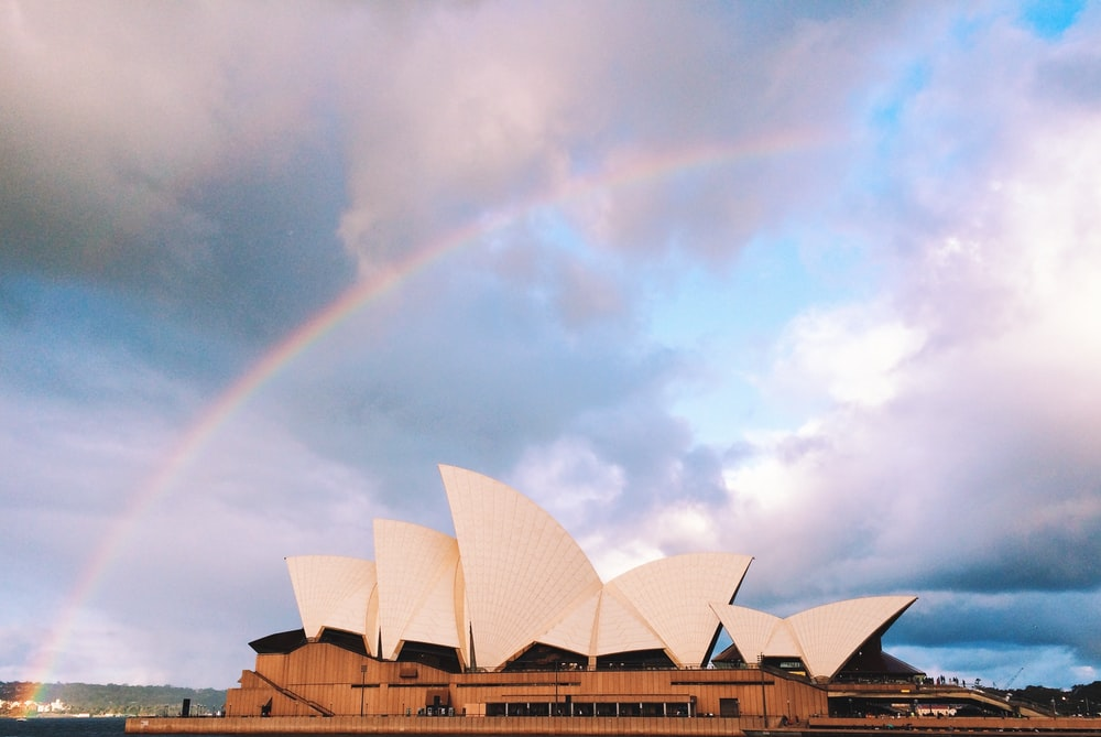 white concrete building under rainbow
