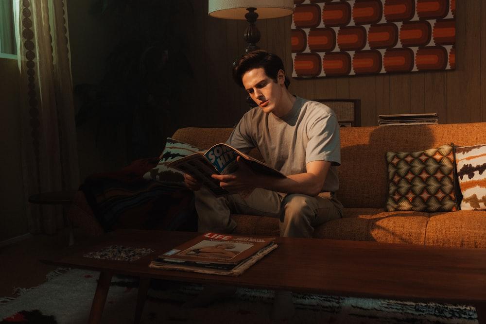 man in white crew neck t-shirt sitting on brown sofa