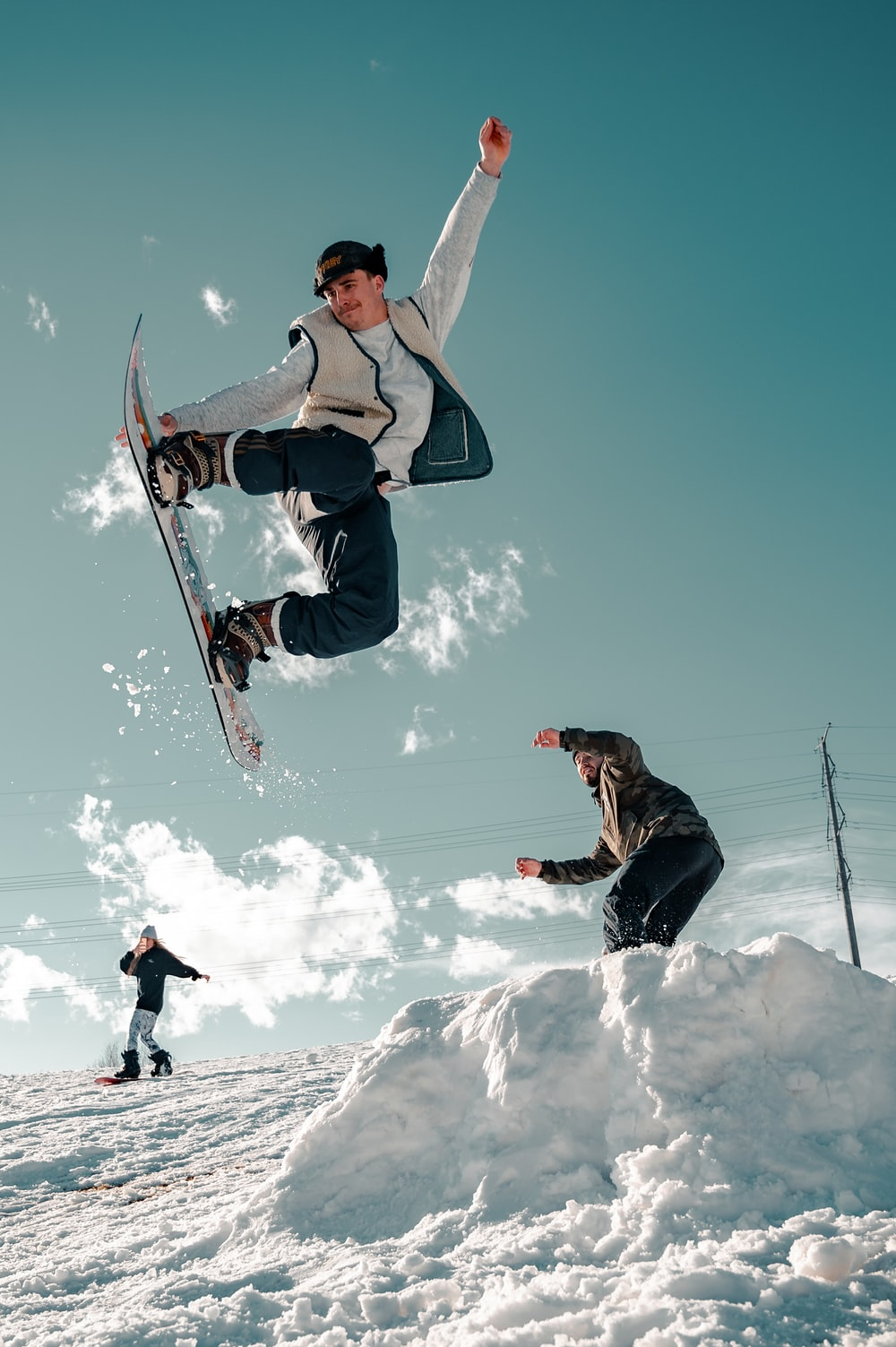 man in black jacket and blue denim jeans riding snowboard during daytime