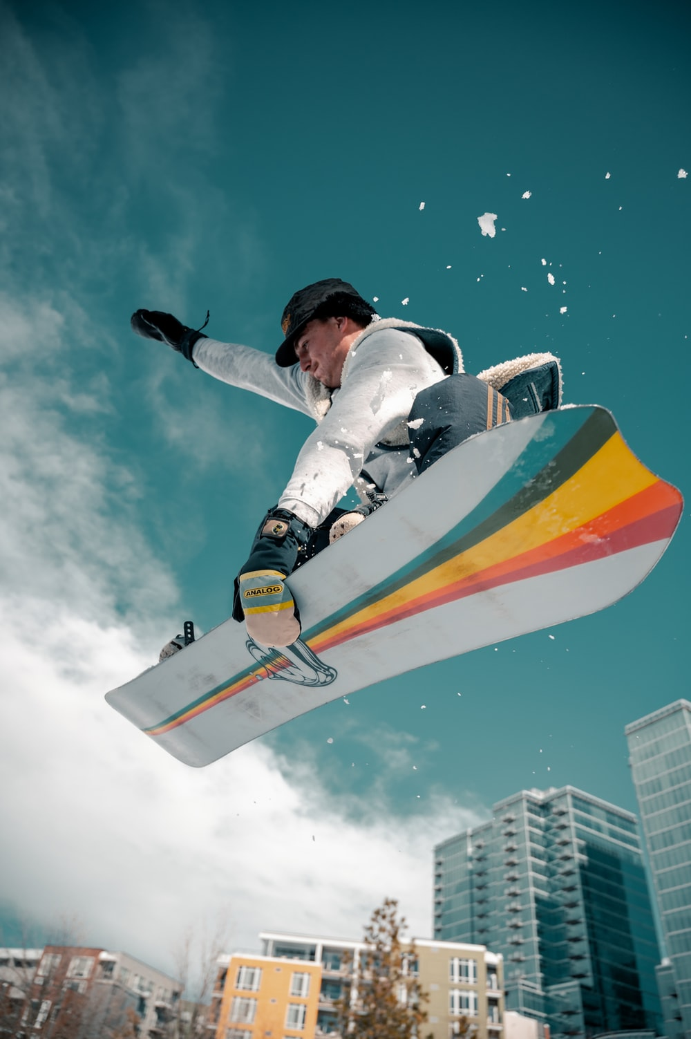 man in white and black jacket riding orange and yellow surfboard