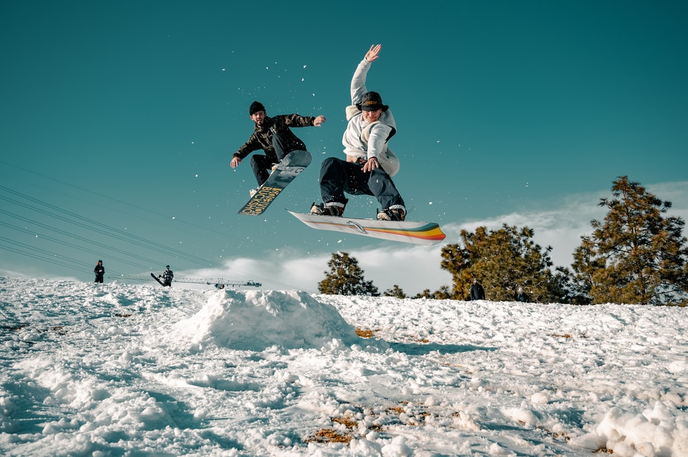 man in black and white jacket riding on snowboard during daytime