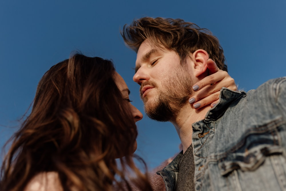 man in grey and black shirt kissing womans cheek