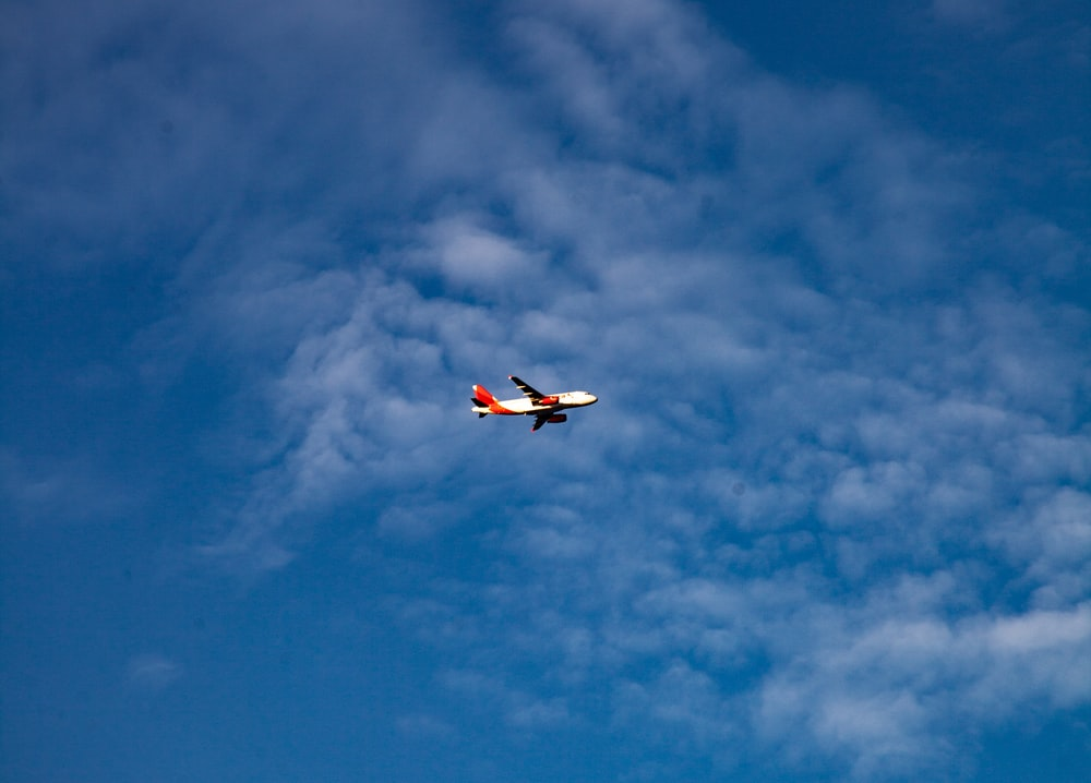 white and red airplane in mid air