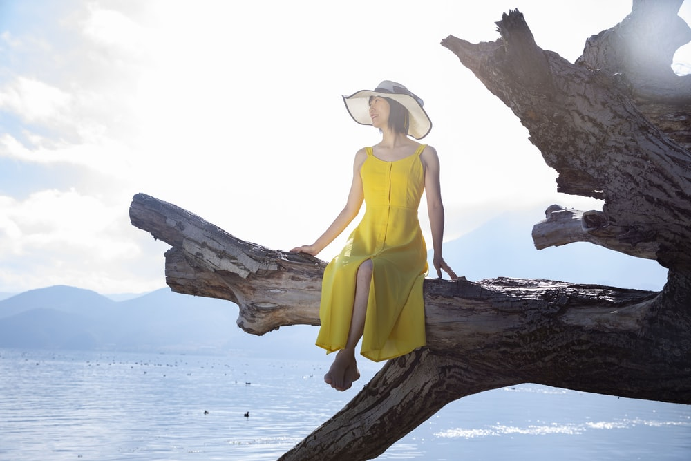 woman in yellow tank top and brown sun hat sitting on brown tree trunk during daytime