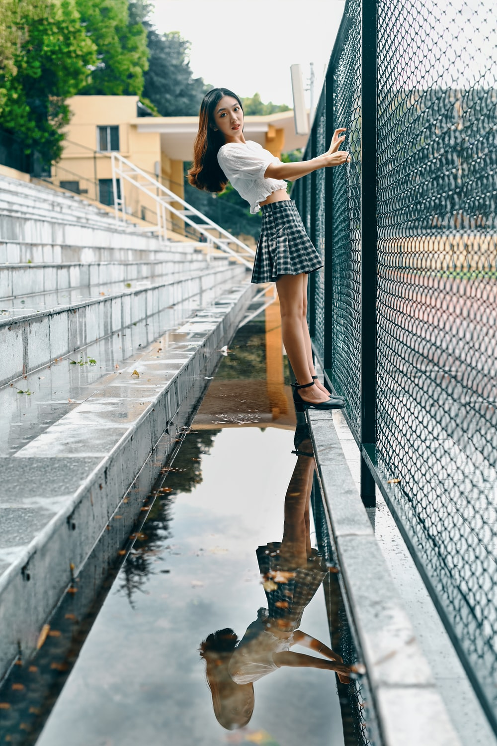 woman in white shirt and black and white skirt standing on bridge during daytime