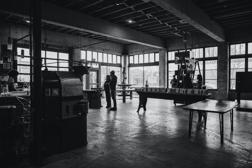 grayscale photo of people in a building