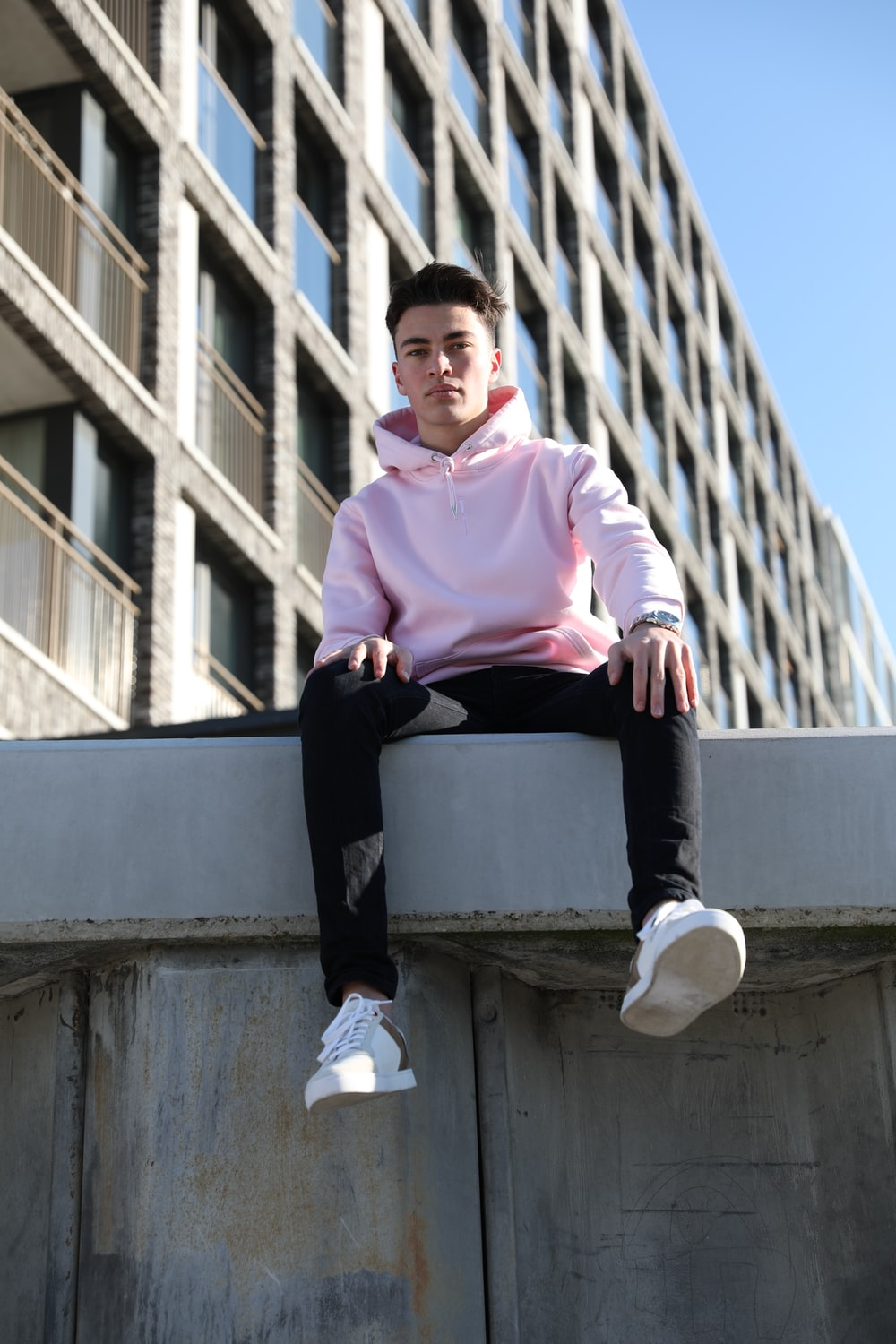 man in pink dress shirt and black pants sitting on concrete wall during daytime