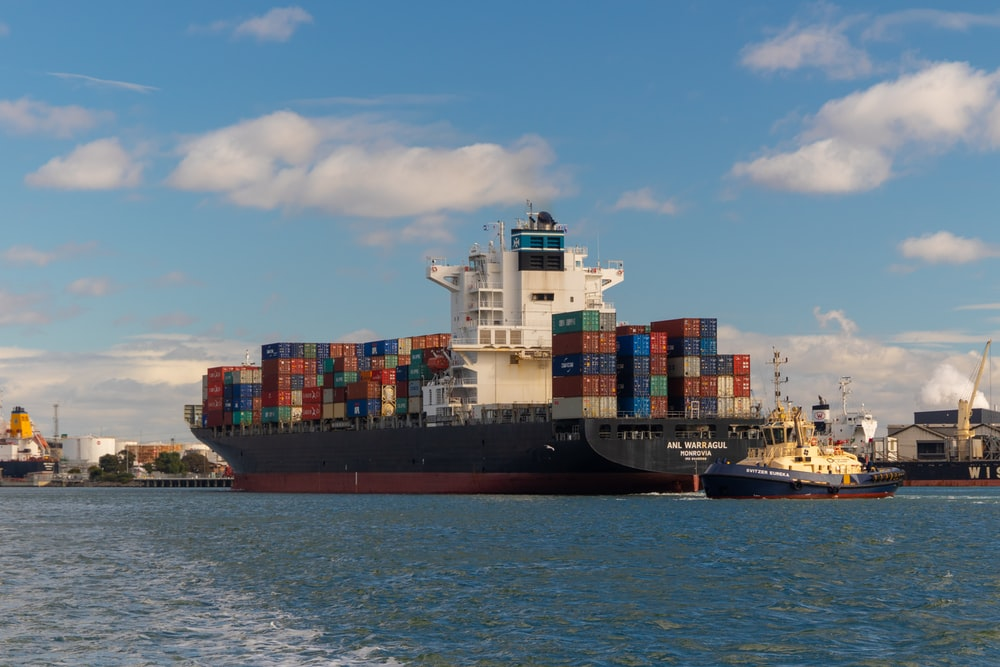 cargo ship on sea under blue sky during daytime
