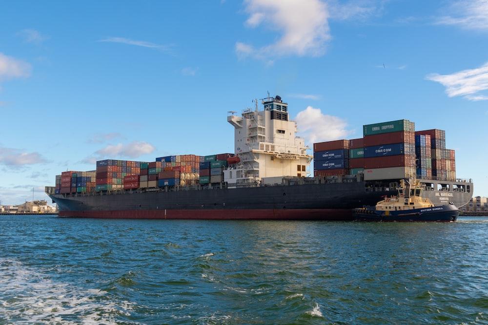 black cargo ship on sea under blue sky during daytime